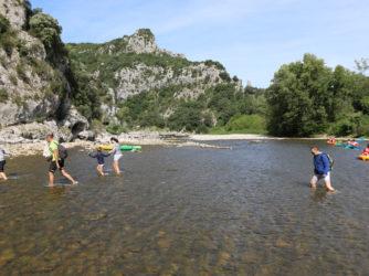 Passage de gué pour des randonneurs dans les Gorges de l'Ardèche